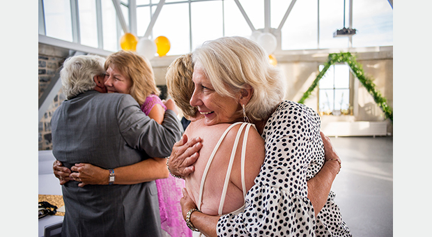 Guests hugging the bride and groom at a wedding anniversary party at the Tett Centre