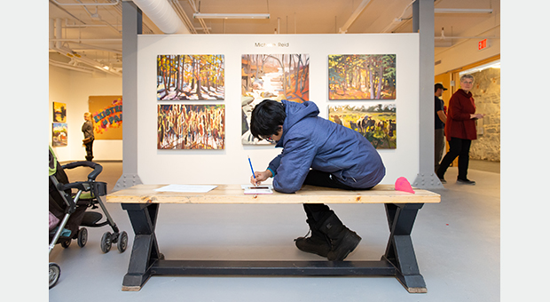 A visitor sketches in the Tett Gallery